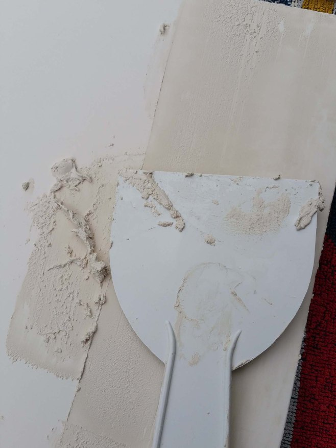 using a spatula to apply the gesso in thin layers